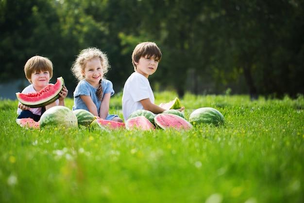 Trzy Szczęśliwego Uśmiechniętego Dziecka łasowania Arbuz W Parku. Premium Zdjęcia