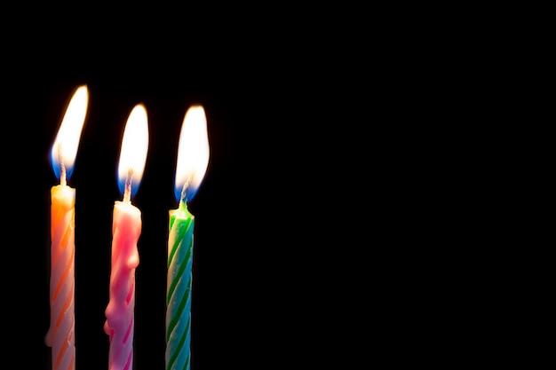 Trzy Urodzinowej świeczki Na Czarnym Tle Premium Zdjęcia