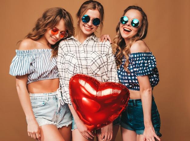 Trzy Uśmiechnięte Piękne Kobiety W Kraciaste Koszule Letnie Ubrania. Girls Posing. Modele Z Czerwonym Balonem W Kształcie Serca W Okularach Przeciwsłonecznych. Gotowy Do świętowania Walentynek Darmowe Zdjęcia