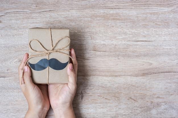 Trzymać prezenta pudełko z wąsem na drewnianym tle Premium Zdjęcia