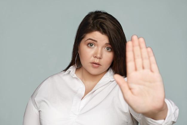 Trzymaj Się Ode Mnie Z Daleka. Poważna Niezadowolona Młoda Brunetka Pulchna Sekretarka W Oficjalnym Stroju Wpatrzona, Wyciągająca Rękę, Wykonująca Gest Stopu Dłonią, Wyrażająca Odmowę Lub Odrzucenie Darmowe Zdjęcia