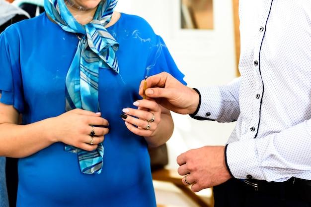 Trzymając W Rękach świece I Dziecko Na Chrzcie W Rosyjskiej Cerkwi. Premium Zdjęcia