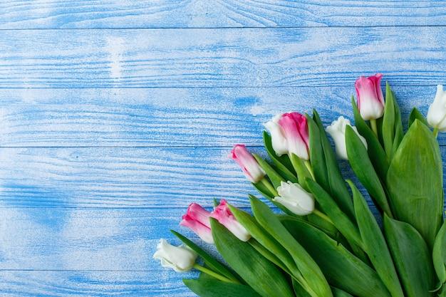 Tulipany z makaroniki na niebieskiej powierzchni drewnianych Premium Zdjęcia