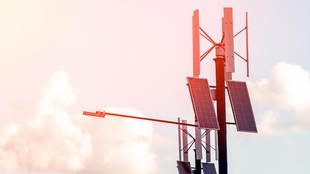 Turbina wiatrowa z panelami słonecznymi na filarze. jawne miasta światło z panelem słonecznym zasilanym na niebieskim niebie z chmurami Premium Zdjęcia