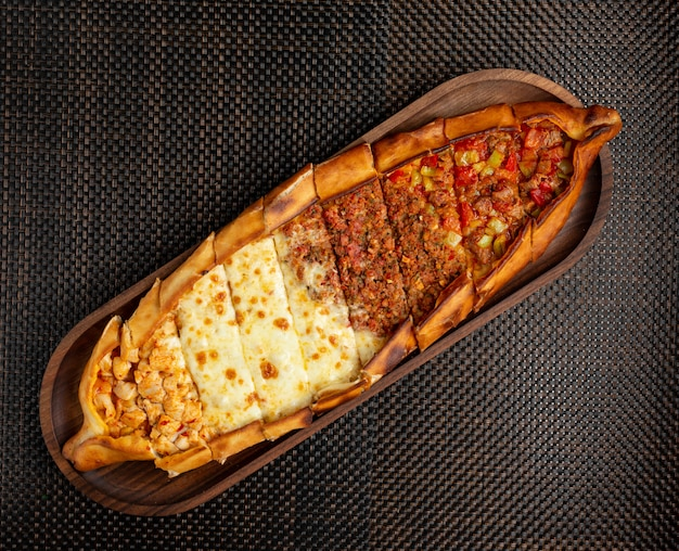 Turecki Pide Z Faszerowanym Mięsem, Serem I Kawałkami Kurczaka Na Drewnianej Misce Darmowe Zdjęcia