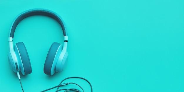 Turkusowe słuchawki na kolorowym tle. koncepcja muzyki z copyspace Premium Zdjęcia