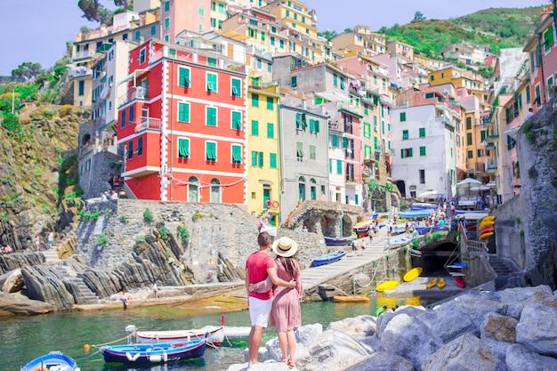 Turyści patrzeje scenicznego widok riomaggiore, cinque terre, liguria, włochy Premium Zdjęcia