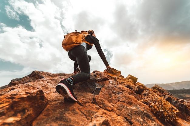 Turysta Kobieta Sukcesu Piesze Wycieczki Na Szczyt Górski Wschód Słońca - Młoda Kobieta Z Plecakiem Wspiąć Się Na Szczyt Góry. Discovery Travel Destination Concept Premium Zdjęcia