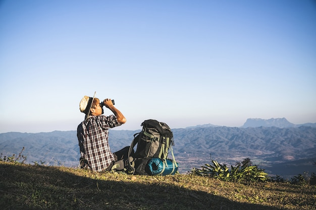 Turysta ogląda przez lornetek na pogodnym chmurnym niebie od góra wierzchołka. Darmowe Zdjęcia