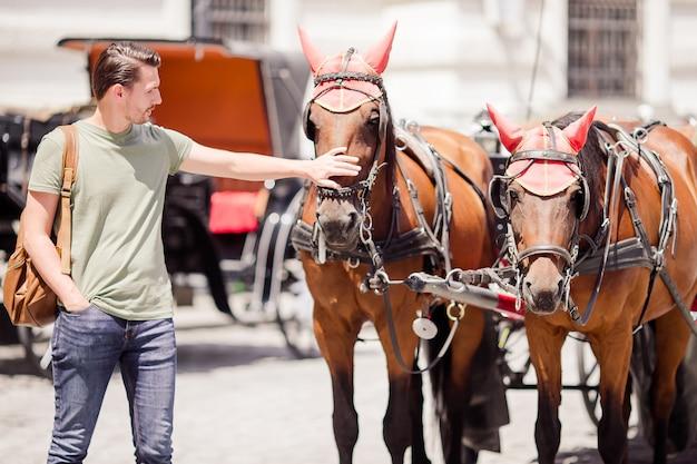 Turysta spacerujący po wiedniu i patrząc na dwa konie w powozie Premium Zdjęcia