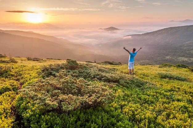 Turysta Stojący Na Szczycie Góry Z Podniesionymi Rękami I Ciesząc Się Wschodem Słońca Premium Zdjęcia