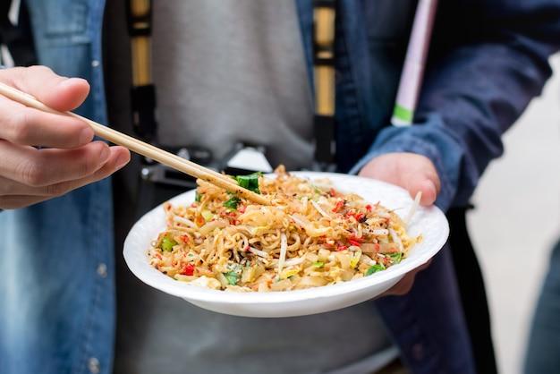 Turysta Wręcza Trzymać Ochraniacza Tajlandzkiego, Jeden Sławny Tradycyjny Tajlandia Ulicy Jedzenie Premium Zdjęcia