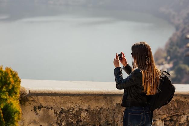 Turystka Kobieta Z Długimi Włosami Robienie Zdjęć Smartfonem Na Szczycie Góry Podróży We Włoszech. Premium Zdjęcia