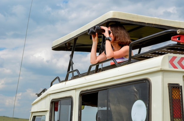 Turystka Na Safari W Afryce, Podróż W Kenii, Oglądanie Przyrody W Sawannie Z Lornetką Premium Zdjęcia