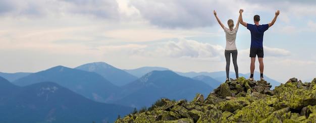 Turystów z podniesionymi rękami na szczycie góry. Premium Zdjęcia