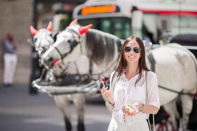 Turystyczna dziewczyna cieszy się wakacje w wiedeń i patrzeje piękne konie w powozie Premium Zdjęcia