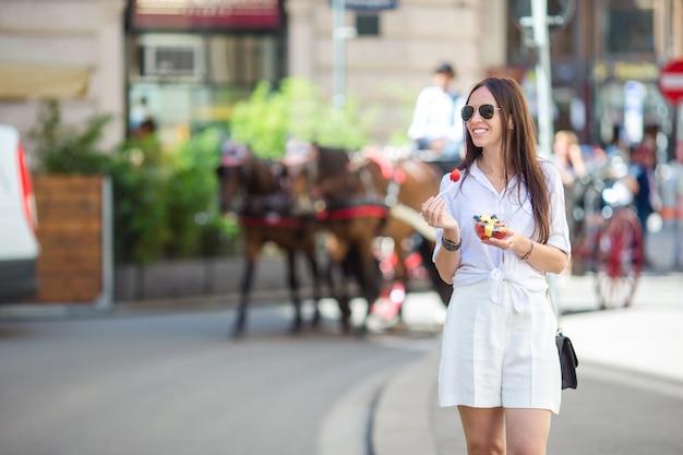 Turystyczna dziewczyna spacerująca po wiedniu i patrząc na piękne konie w powozie Premium Zdjęcia