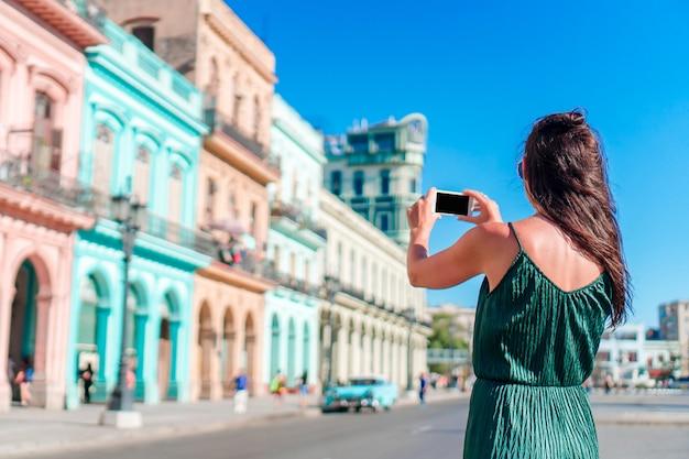 Turystyczna dziewczyna w popularnym terenie w hawańskim, kuba. młoda kobieta podróżnika ono uśmiecha się szczęśliwy. Premium Zdjęcia