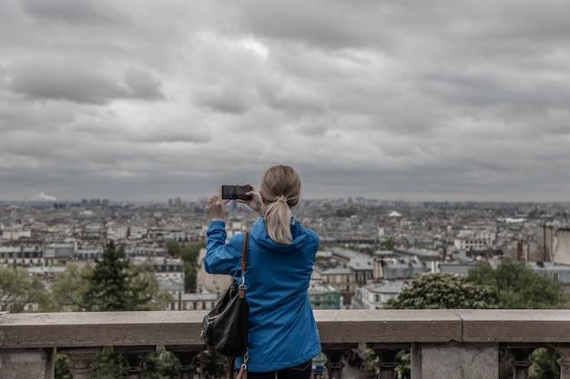 Turystyczna Kobieta Robi Zdjęcie Miasta W Pochmurną Pogodę Z Aparatu W Telefonie Komórkowym Premium Zdjęcia