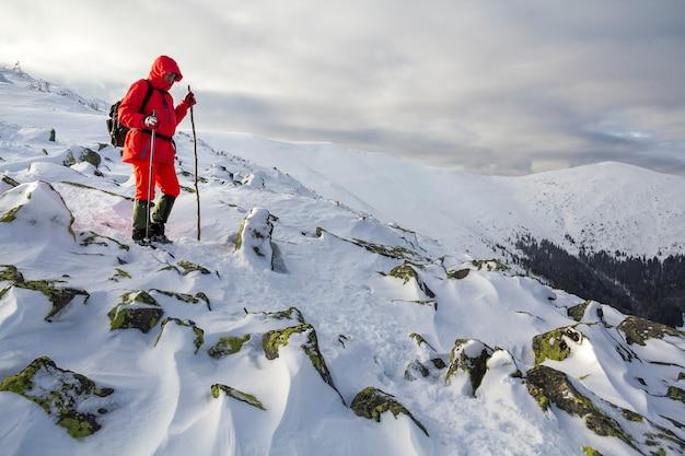 Turystyczny Turysta W Jaskrawoczerwonej Odzieży Z Laskami Schodzącymi Z Niebezpiecznego Zbocza Skalistej Góry Pokrytej śniegiem Na Burzliwym Zachmurzonym Niebie Kopia Przestrzeń Tło. Premium Zdjęcia