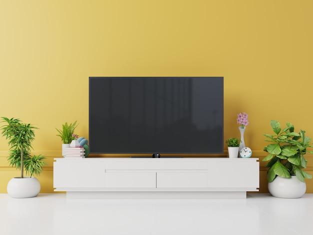 Tv na szafce w nowoczesnym salonie z lampą, stołem, kwiatem i rośliną na żółtym tle ściany Premium Zdjęcia