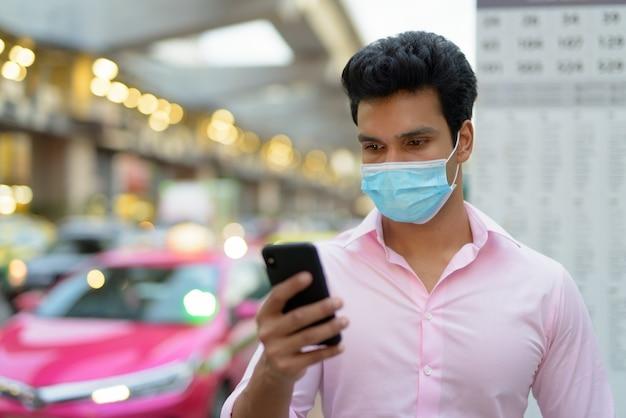 Twarz Młodego Biznesmena Z Indii Z Maską Za Pomocą Telefonu Na Przystanku Autobusowym Premium Zdjęcia