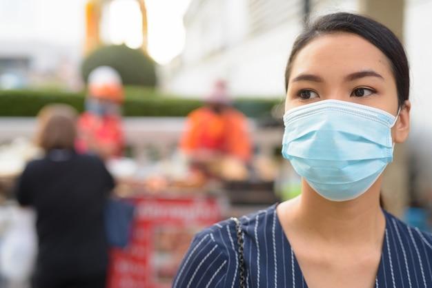 Twarz Młodej Bizneswoman Azjatyckiego Z Maską Do Ochrony Przed Myśleniem O Epidemii Wirusa Koronowego W Mieście Premium Zdjęcia