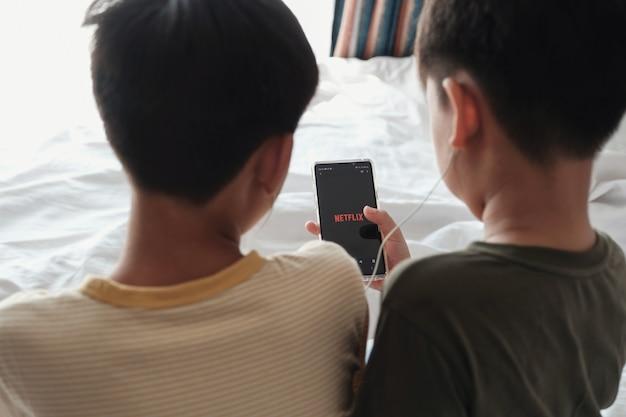 Tween Chłopcy Dzielący Słuchawki I Oglądający Netflix Na Smartfonie Premium Zdjęcia