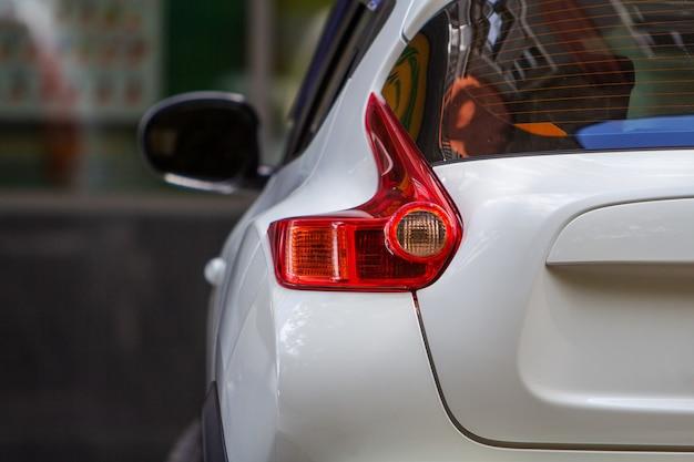 Tylna Lampa Samochodu Zaparkowanego Przy Krawężniku Na Ulicy Na Parkingu. Premium Zdjęcia
