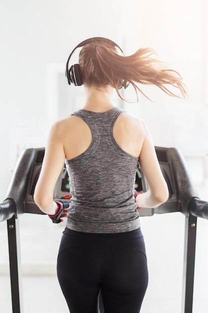 Tylna sport kobieta jogging na karuzeli w gym, zdrowy styl życia Premium Zdjęcia
