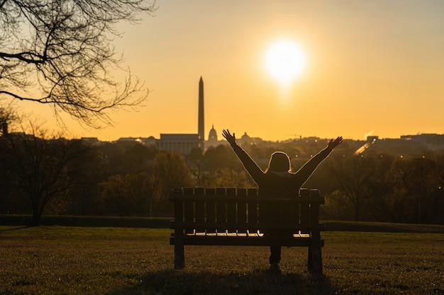Tylna Strona Azjatyckiej Kobiety Siedzącej I Podnoszącej Ręce Do Sukcesu Nad Punktem Orientacyjnym W Waszyngtonie, Który Widzi Kapitol Stanów Zjednoczonych, Pomnik Waszyngtonu I Pomnik Lincolna W Czasie Wschodu Słońca, Premium Zdjęcia
