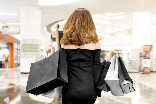 Tylni widok azjatycka kobieta w czerni ubraniach niesie czarnych torba na zakupy w centrum handlowym Premium Zdjęcia