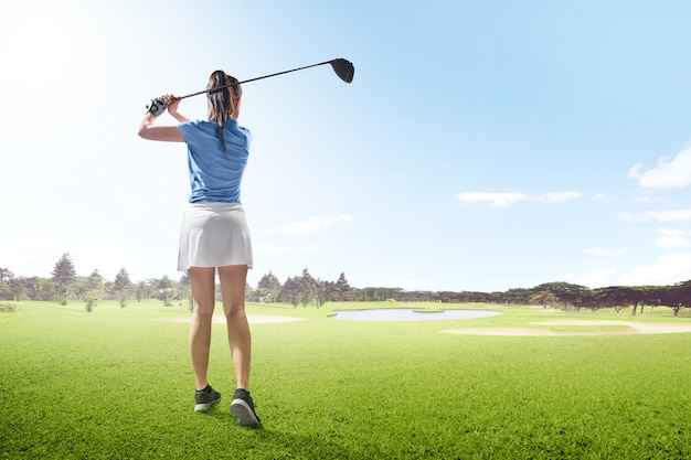Tylni widok azjatykcia kobieta na długiej przejażdżki huśtawce z drewnianym klubem w polu golfowym z piasków bunkierami, stawem i drzewami Premium Zdjęcia
