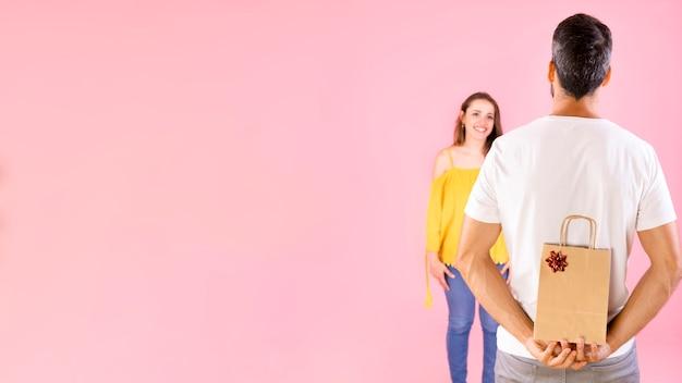 Tylni widok chuje prezent od jej dziewczyny nad różowym tłem mężczyzna Darmowe Zdjęcia