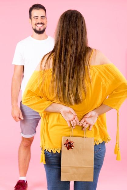 Tylni widok chuje robić zakupy papierową torbę z czerwonym łękiem od jej chłopaka kobieta Darmowe Zdjęcia