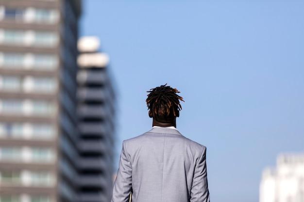 Tylni widok czarnego afrykanina młody człowiek patrzeje daleko od przeciw niebieskiemu niebu w mieście Premium Zdjęcia