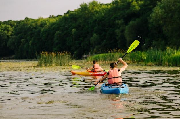 Tylni Widok Dwa Mężczyzna Kayaking Na Jeziorze Premium Zdjęcia