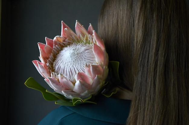 Tylni Widok Dziewczyna Trzyma Różowego Protea Kwiatu Na Ciemnym Tle Z Ciemnym Włosy, Selekcyjna Ostrość Premium Zdjęcia