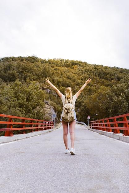 Tylni Widok Młoda Blondynki Kobieta Z Plecakiem I Rękami W Górę Odprowadzenia Na Drodze Nad Mostem Blisko Góry. Koncepcja Podróży I Przygody. Podróżnik Pośrodku Lasu. Podróżować Samemu Premium Zdjęcia