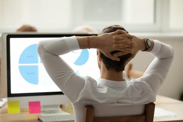 Tylni widok przy biznesmenem analizuje statystyki raportuje na ekranie komputerowym Darmowe Zdjęcia