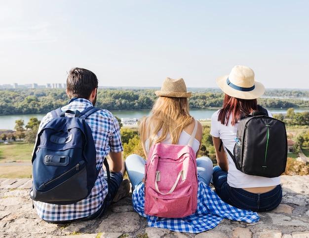 Tylni widok przyjaciele z plecaka obsiadaniem przy outdoors Darmowe Zdjęcia