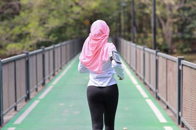 Tylni Widoku Portreta Sporty Młoda Azjatykcia Muzułmańska Kobieta W Sportswear Jogging Plenerowy Dla Maratonu Szkolenia. Jogger Dziewczyna ćwiczy Wzdłuż Betonowej ścieżki Plenerowej Z Zielonym Drzewnym Tłem. Koncepcja Sportu Premium Zdjęcia