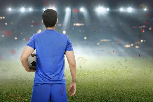 Tylny widok azjatykcia gracz futbolu pozycja z piłką Premium Zdjęcia
