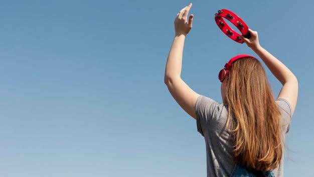 Tylny Widok Beztroska Kobieta Trzyma Tamburyn Z Hełmofonami Darmowe Zdjęcia