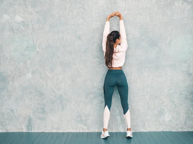 Tylny Widok Sprawności Fizycznej Kobieta Odziewa Ufny W Sportach. Kobieta Rozciąga Out Przed Trenować Blisko Szarości ściany W Studiu Darmowe Zdjęcia