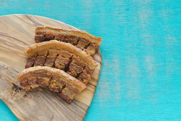Typowe Kolumbijskie Jedzenie. Kolumbijskie Smażone Skórki Wieprzowe Na Niebieskim Tle Premium Zdjęcia