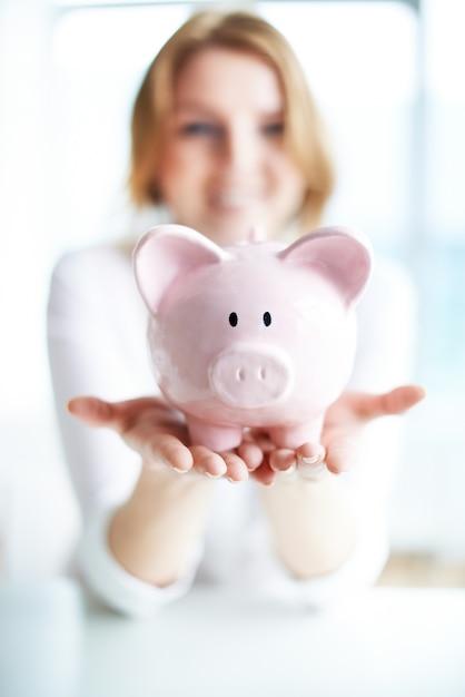 Uśmiechnięta kobieta oszczędza pieniądze w skarbonki Darmowe Zdjęcia