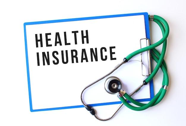 Ubezpieczenie Zdrowotne Tekst Na Folderze Medycznym Z Dokumentami I Stetoskopem Na Białym Tle. Pojęcie Medyczne. Premium Zdjęcia