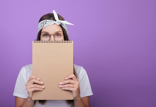 Uczeń trzyma zeszyt, album do rysowania. Premium Zdjęcia