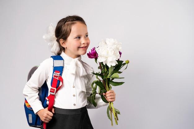 Uczennica Pierwszej Klasy W Białej Koszuli Z Kwiatami I Plecakiem Premium Zdjęcia